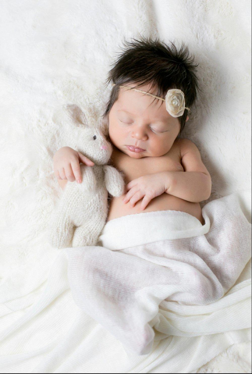 Portrait of a sleeping newborn baby with a white-flowered tiara and a white-colored soft toy