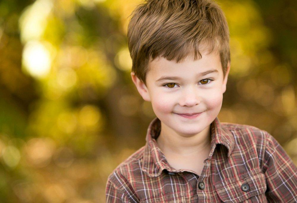 Portrait of a young boy wearing a brown check shirt