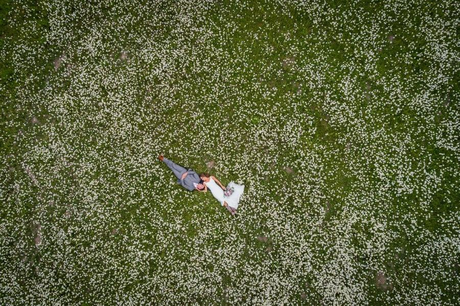 A bird eye's view of a bride and groom posing on a garden filled with white flowers