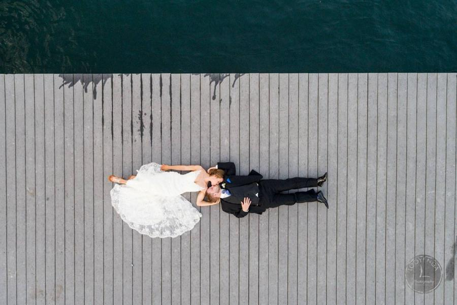 Drone shot of a bride and groom posing on a pavement near a sea
