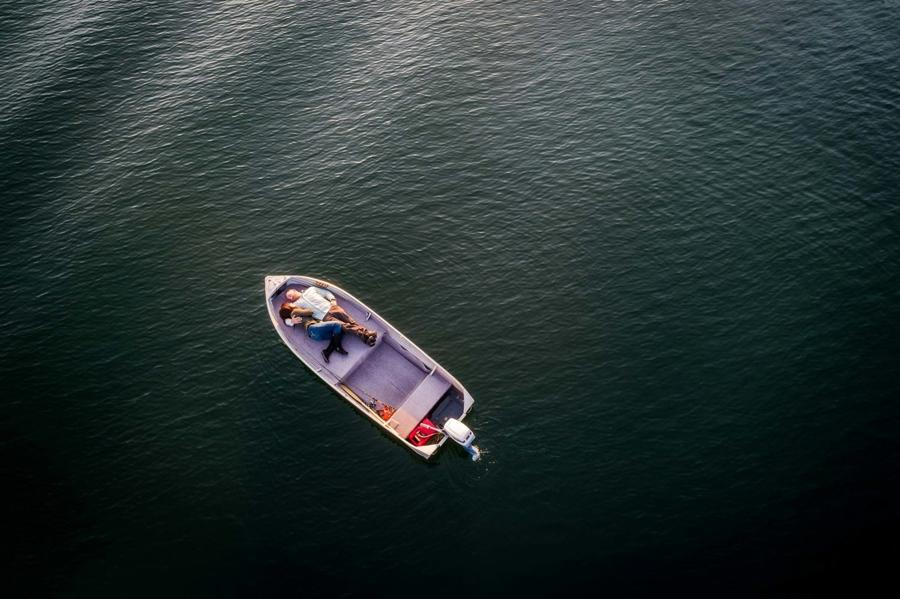 Drone photograph of a couple posing on a boat