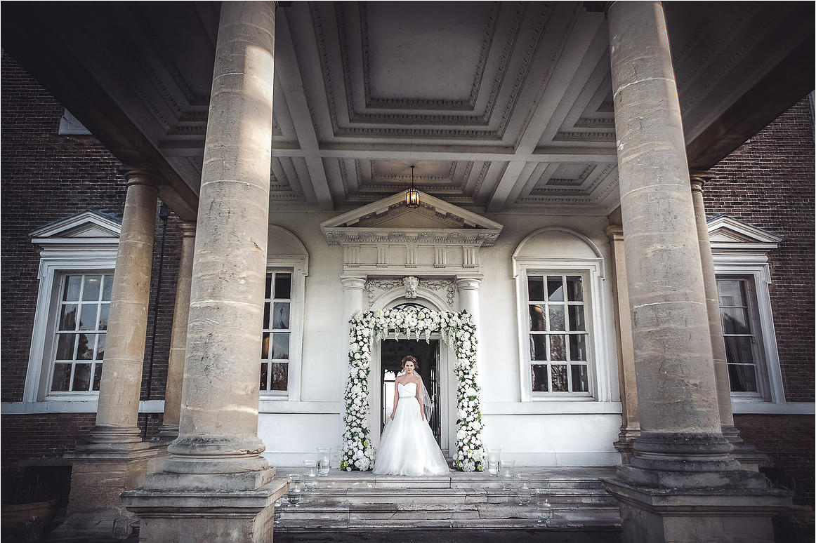 A bride standing in front of a flower decorated doorway