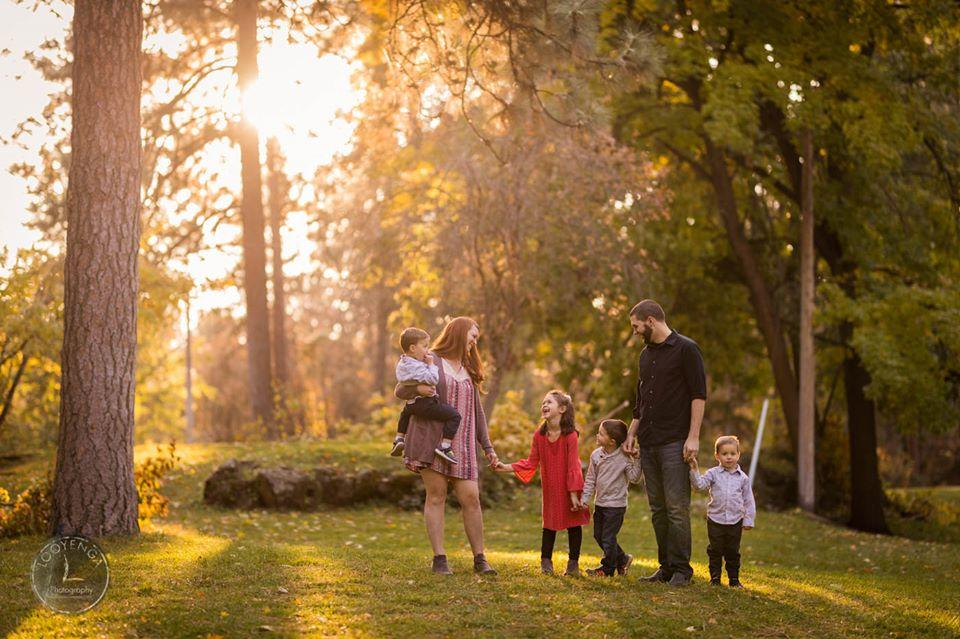 A family of 6 walking amidst a forest depicting the holiday season in a blog titled - Ways to up your photography income