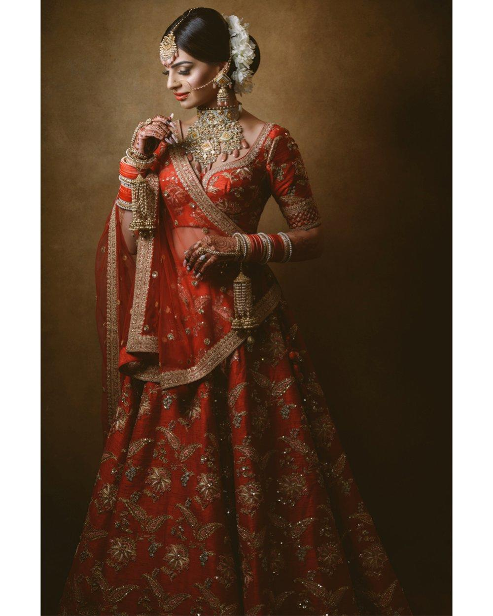 A bride posing in a red Indian wedding dress - ShootDotEdit feature of how to navigate gear-specific questions from clients