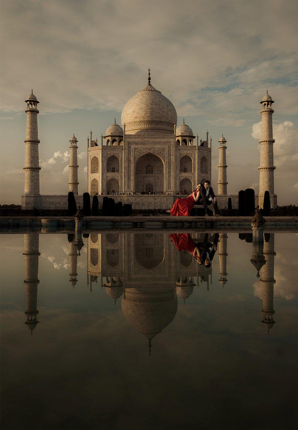 A couple posing in front of the Taj Mahal in India