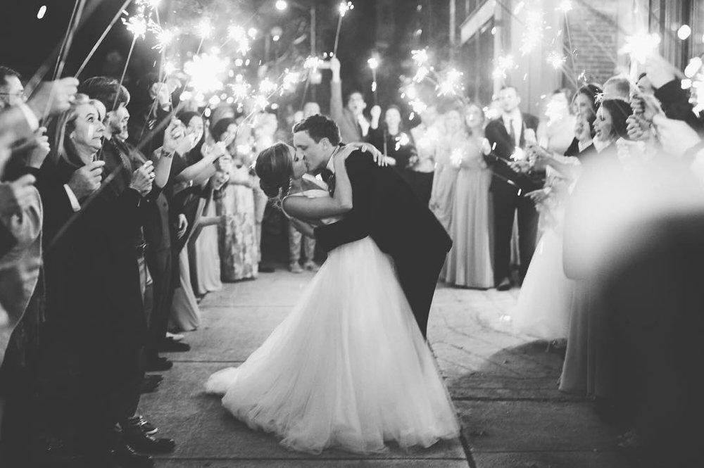 A black and white photo of the bride and groom kissing under sparklers