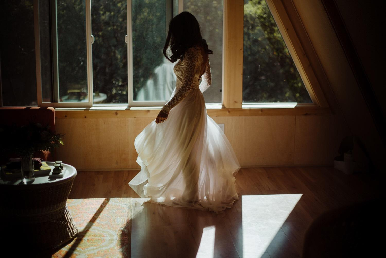 A soft-lighting shot of a bride swirling her wedding dress