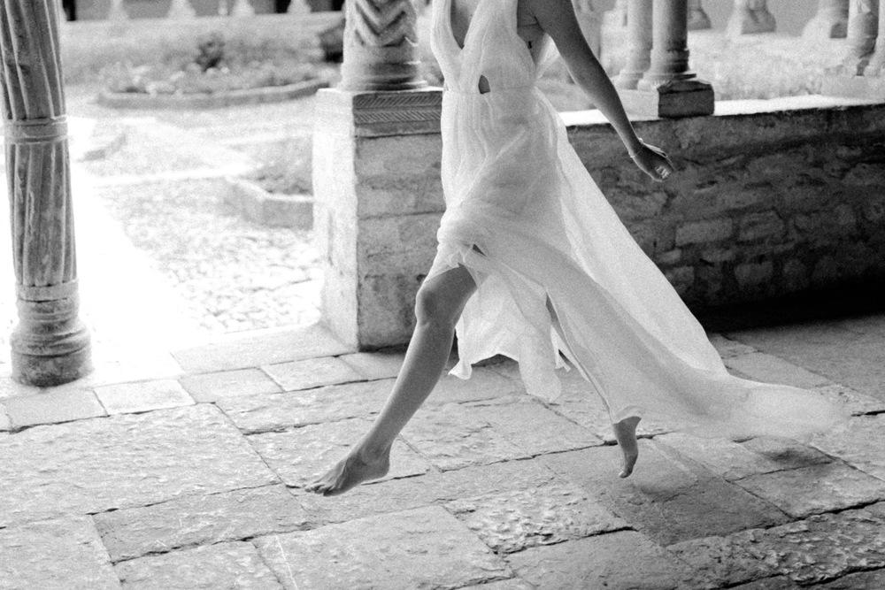 black and white photo of woman leaping in wedding dress