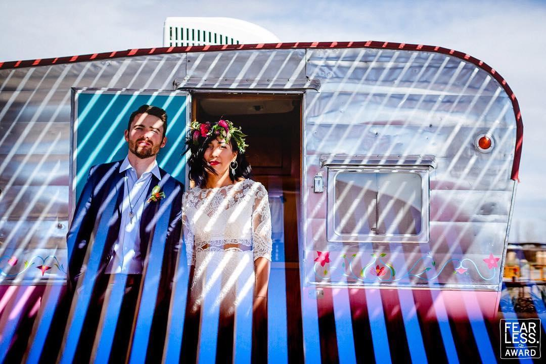 couple standing by airstream camper