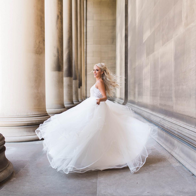 blond bride twirling around near white columns