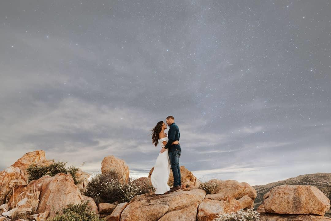 couple standing on rock in starlight