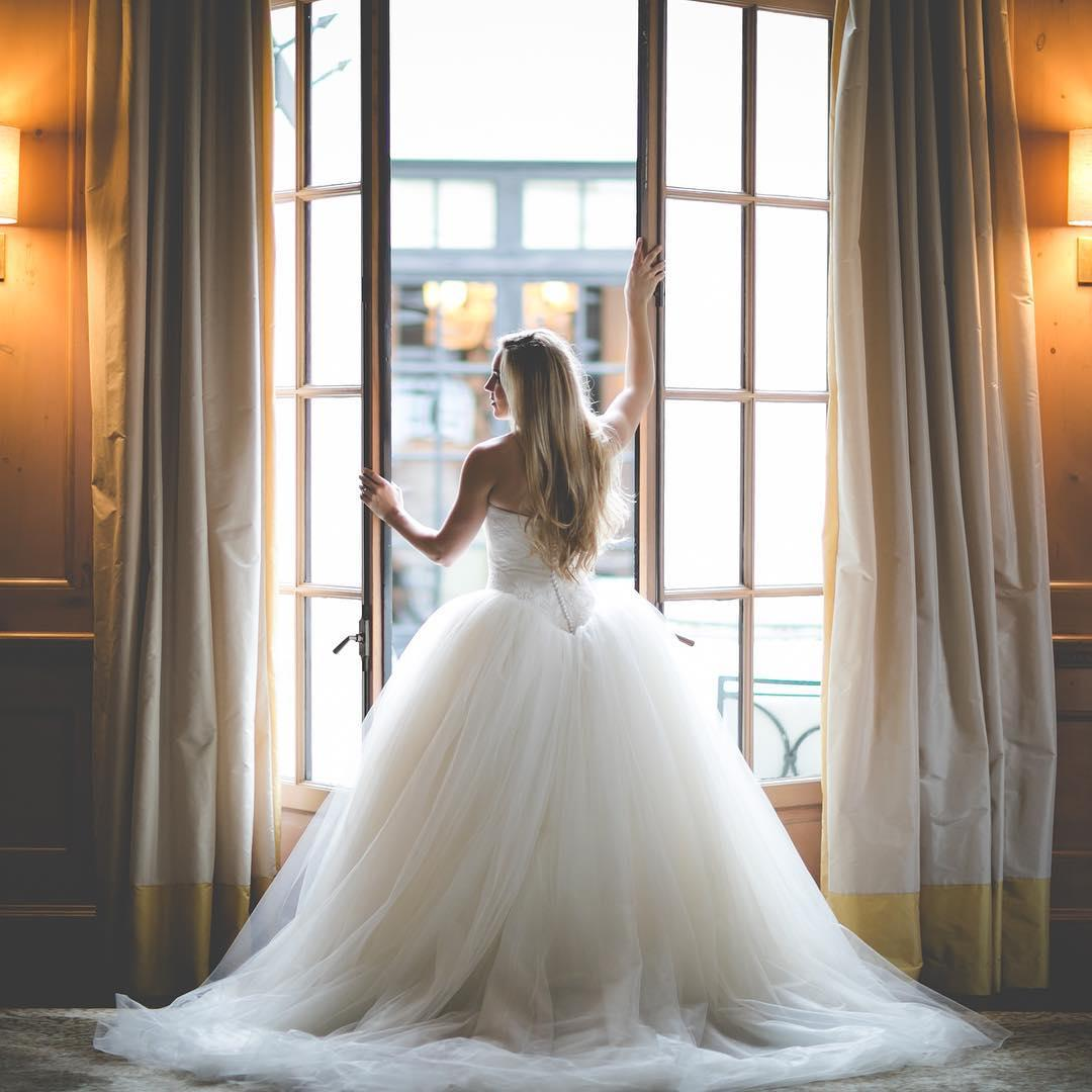bride standing at open french doors staring over her shoulder