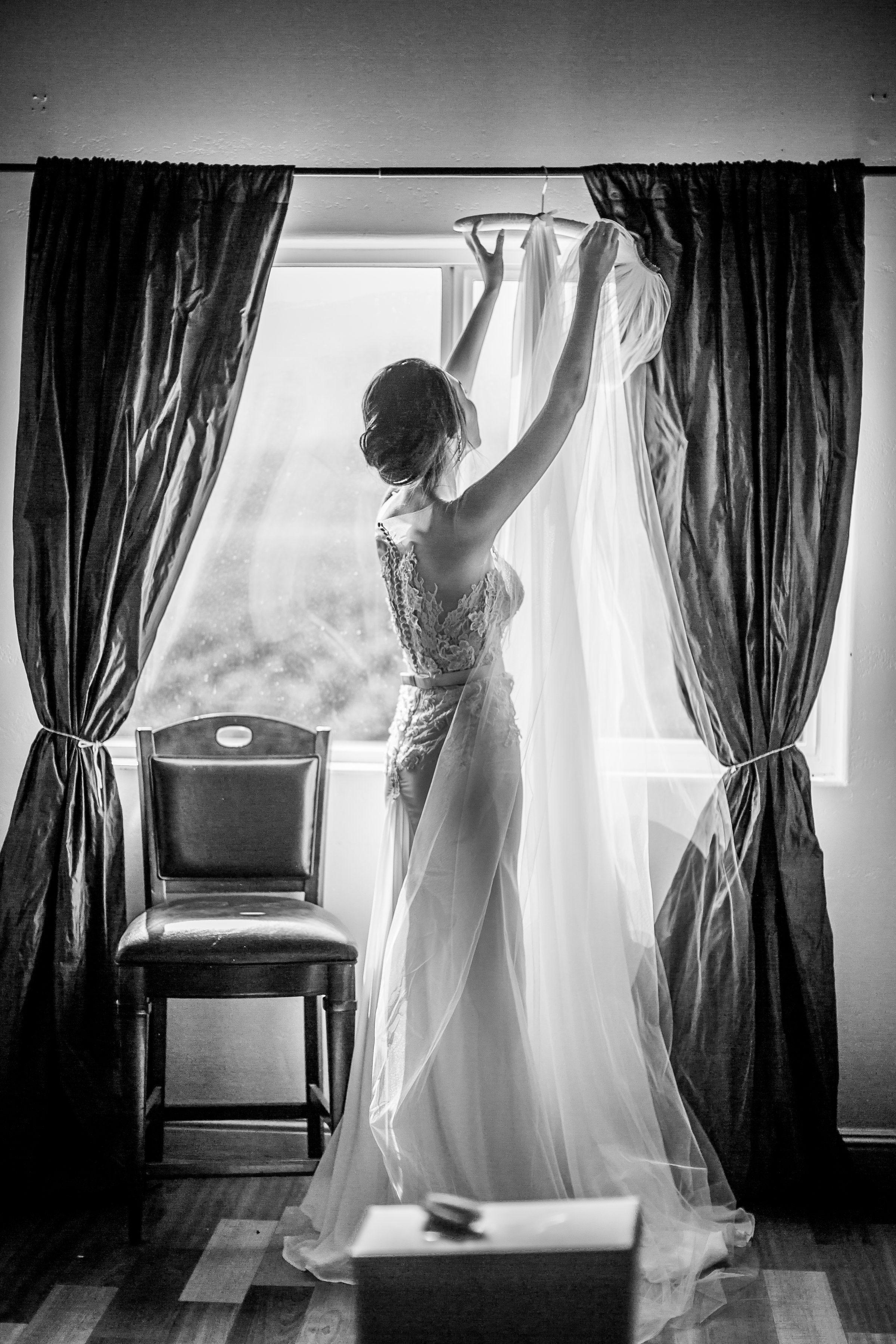 black and white photo of bride hanging up veil