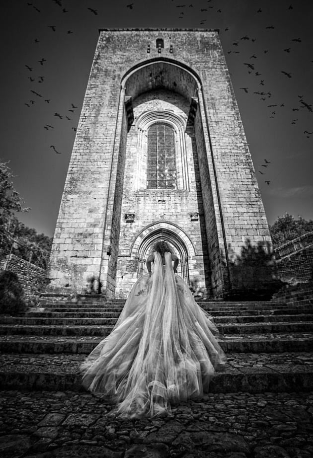 black and white photo of bride climbing stairs to a cathedral with crows circling