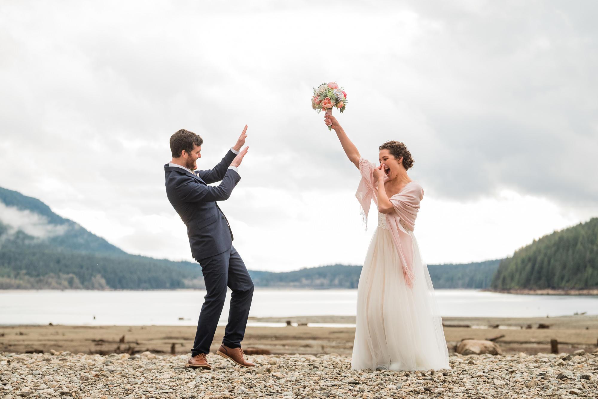 wedding couple doing a funny dance on a beach