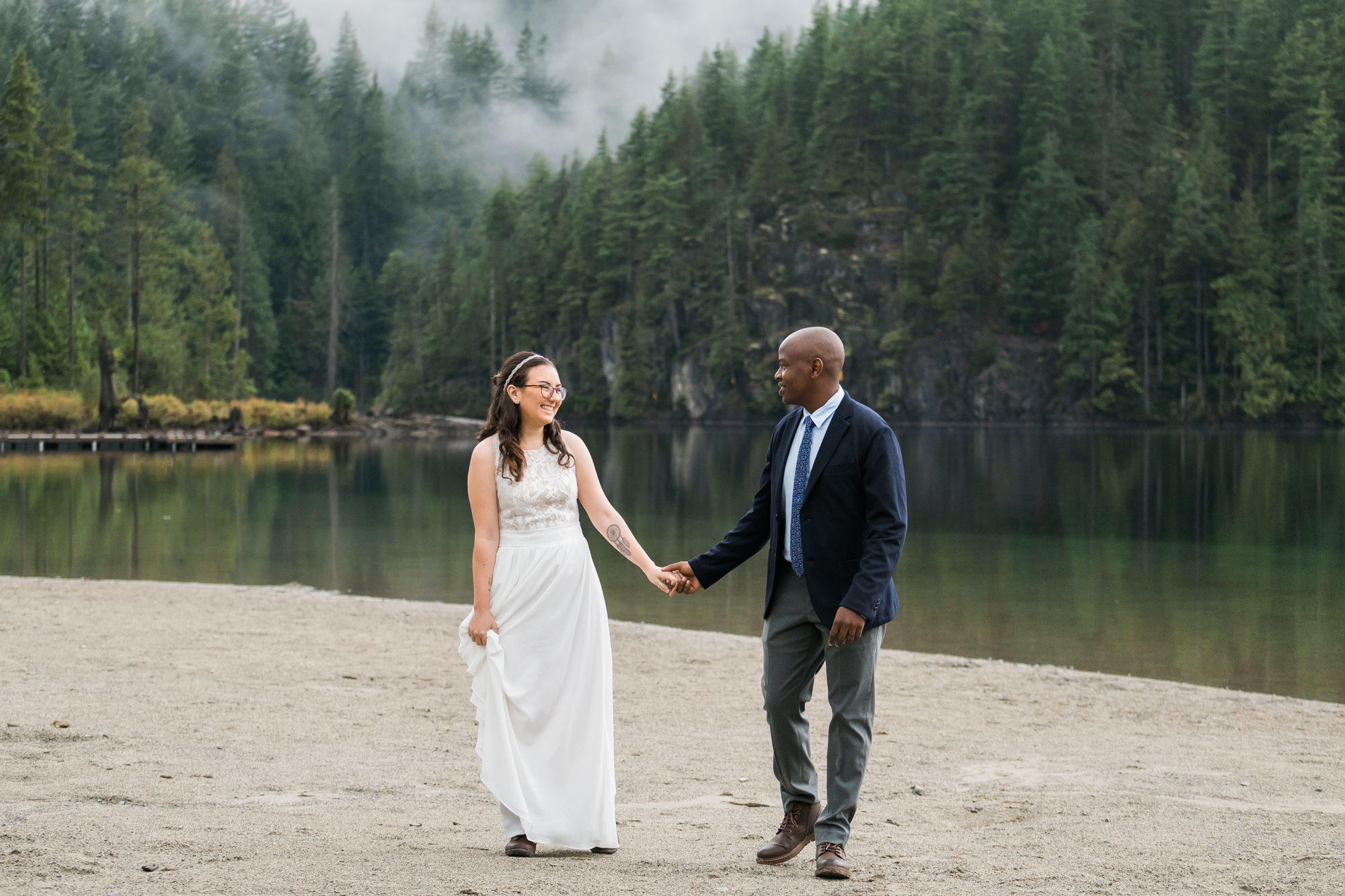 black groom holding the hand of a white bride on the edge of a lake with mist