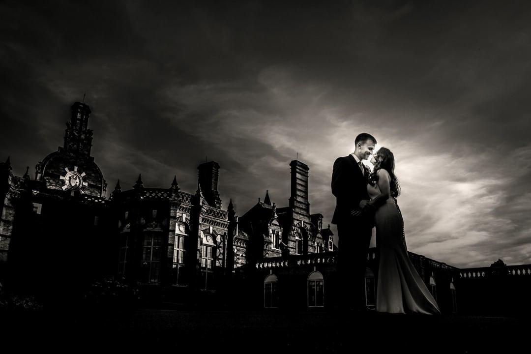 sepia toned image of couple lit against stormy sky in Europe