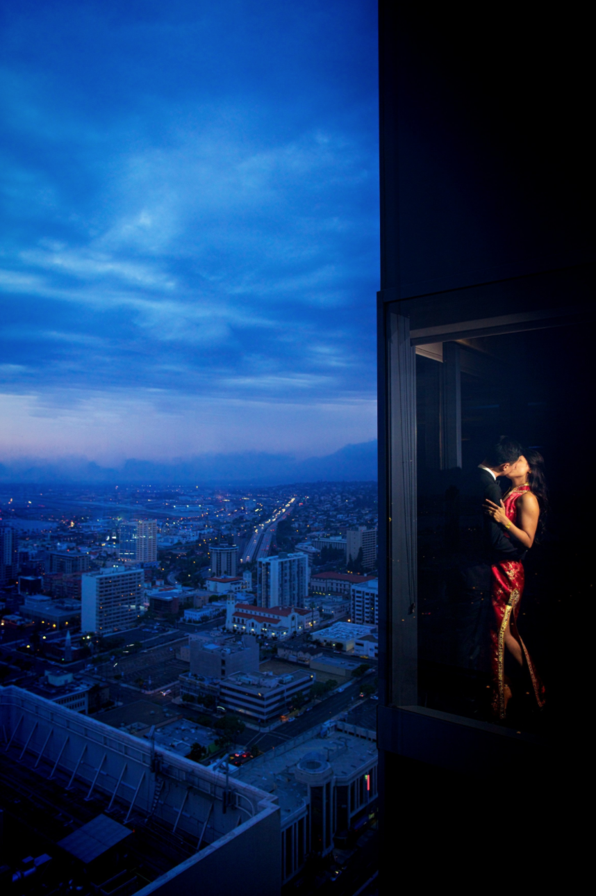 man and woman in window kissing with city view in the background