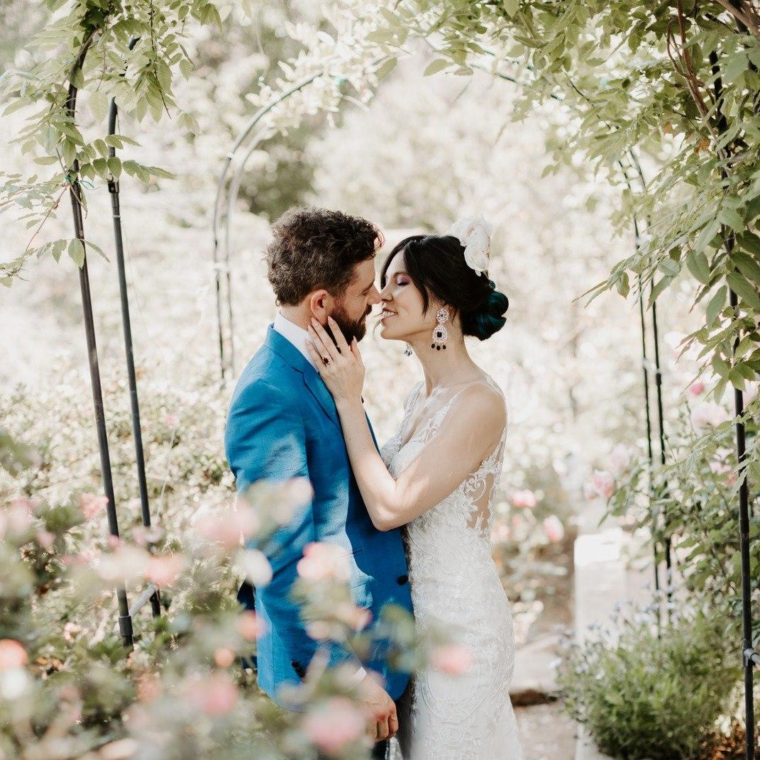 groom in blue and bride in white almost kissing