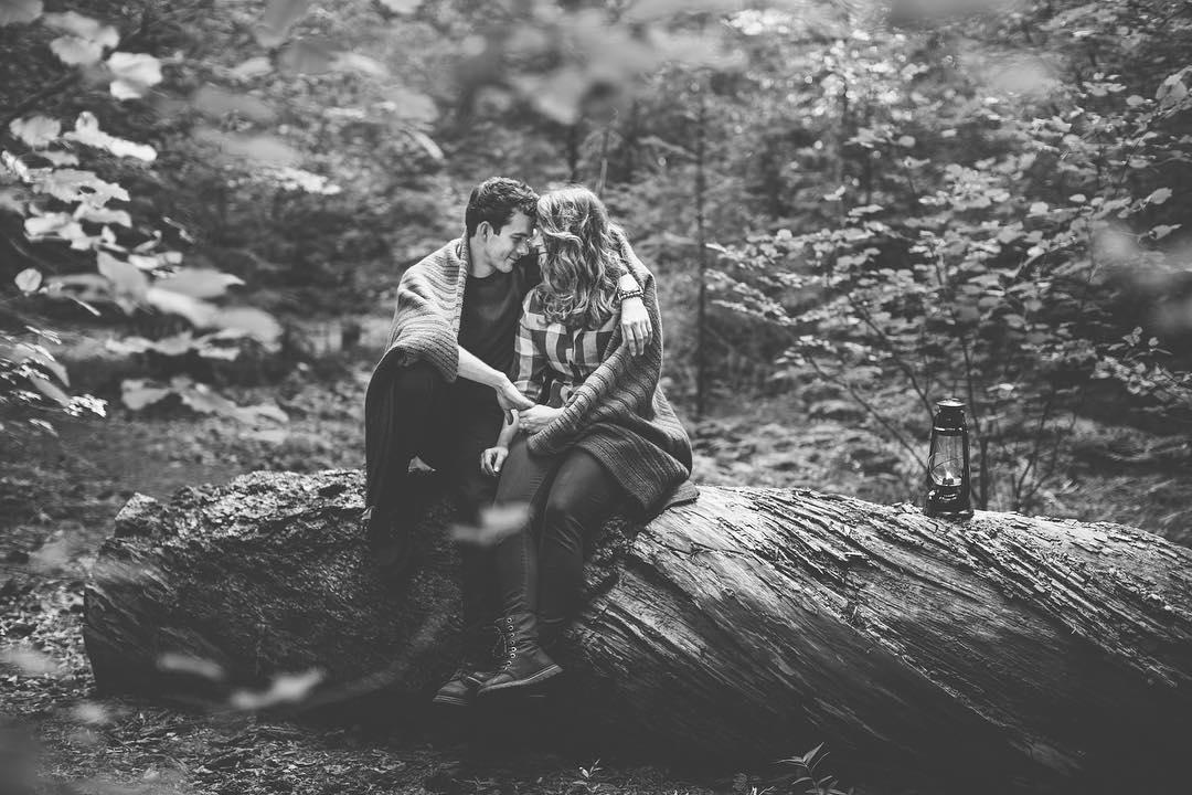 black and white image of a man and woman sitting on a rock cuddling