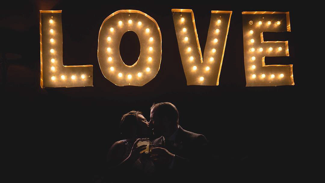 neon love sign with couple kissing and holding a drink underneath