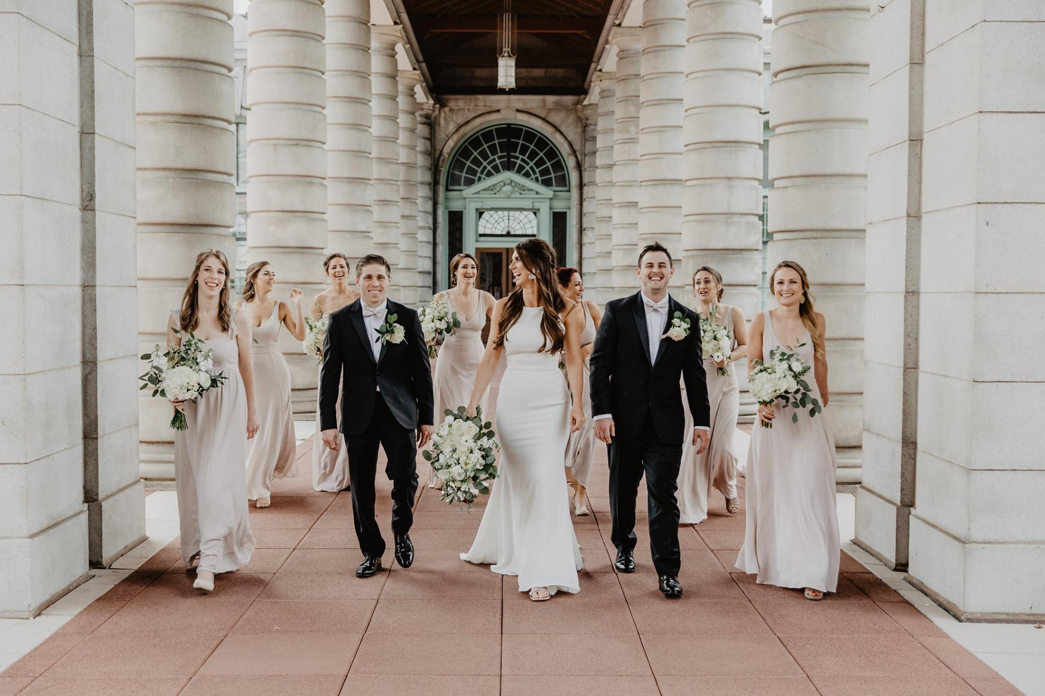 bride, groom and wedding party walking towards photographer, laughing, with white columns on either side