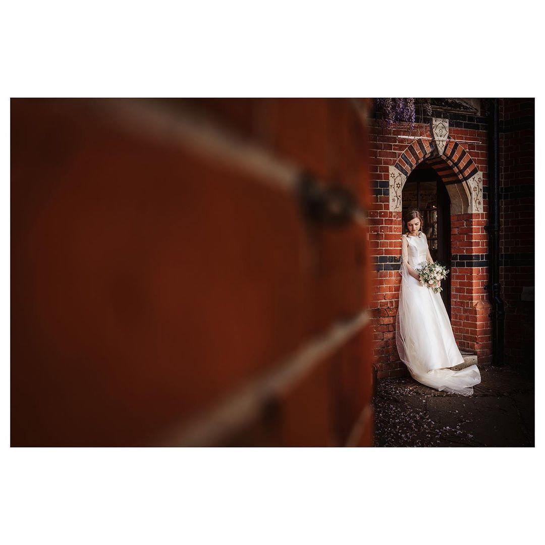 woman standing in a red brick archway wearing a wedding dress