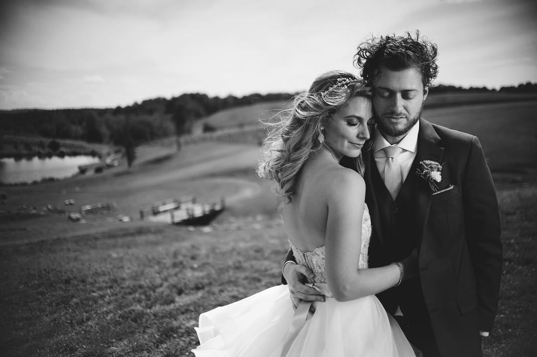 black and white image of a woman wearing flower crown with eyes closed leaning against man wearing suite on their wedding day in an open field near a lake