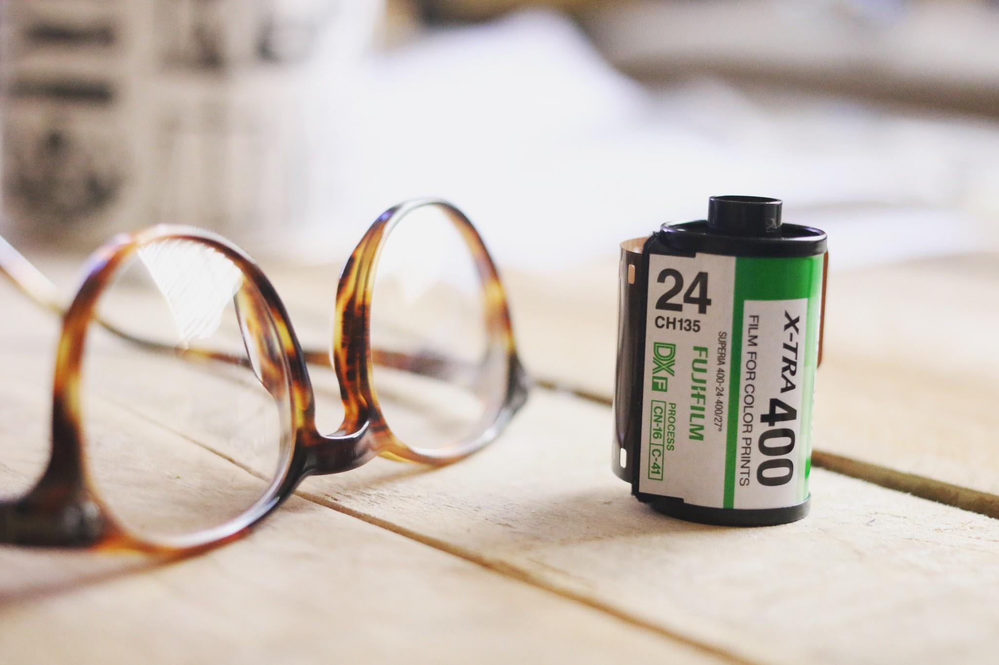 fuji 400 film cannister next to glasses on wood table