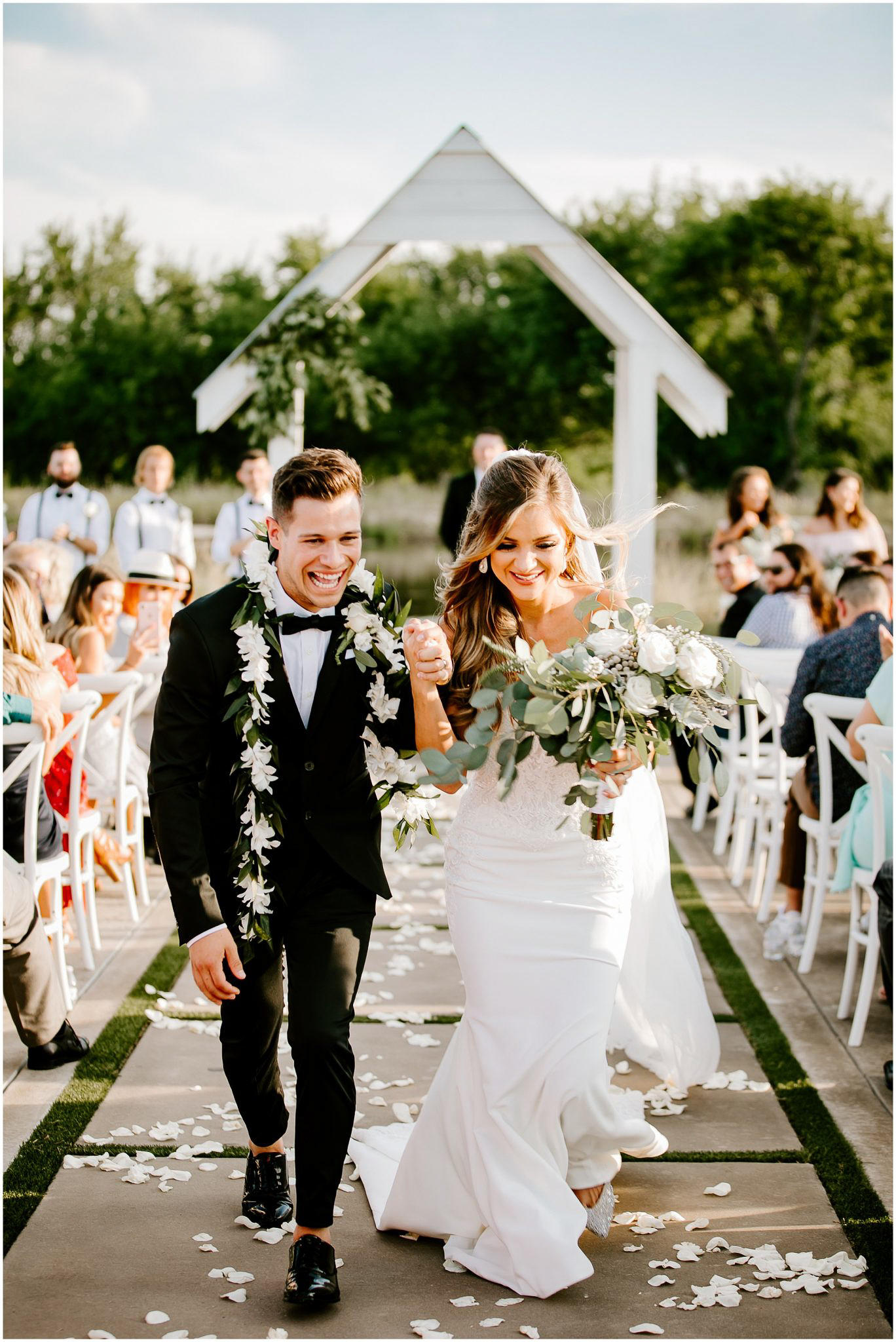 couple walking down aisle after ceremony in outdoor setting wearing leas
