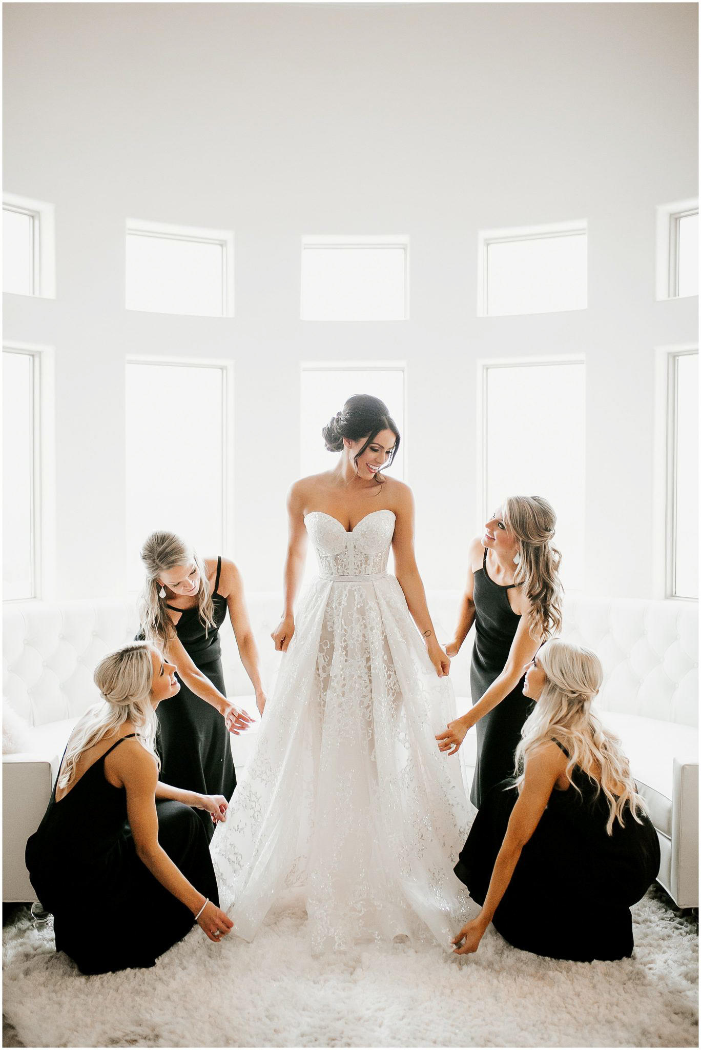 bride getting ready surrounded by her bridesmaids wearing black