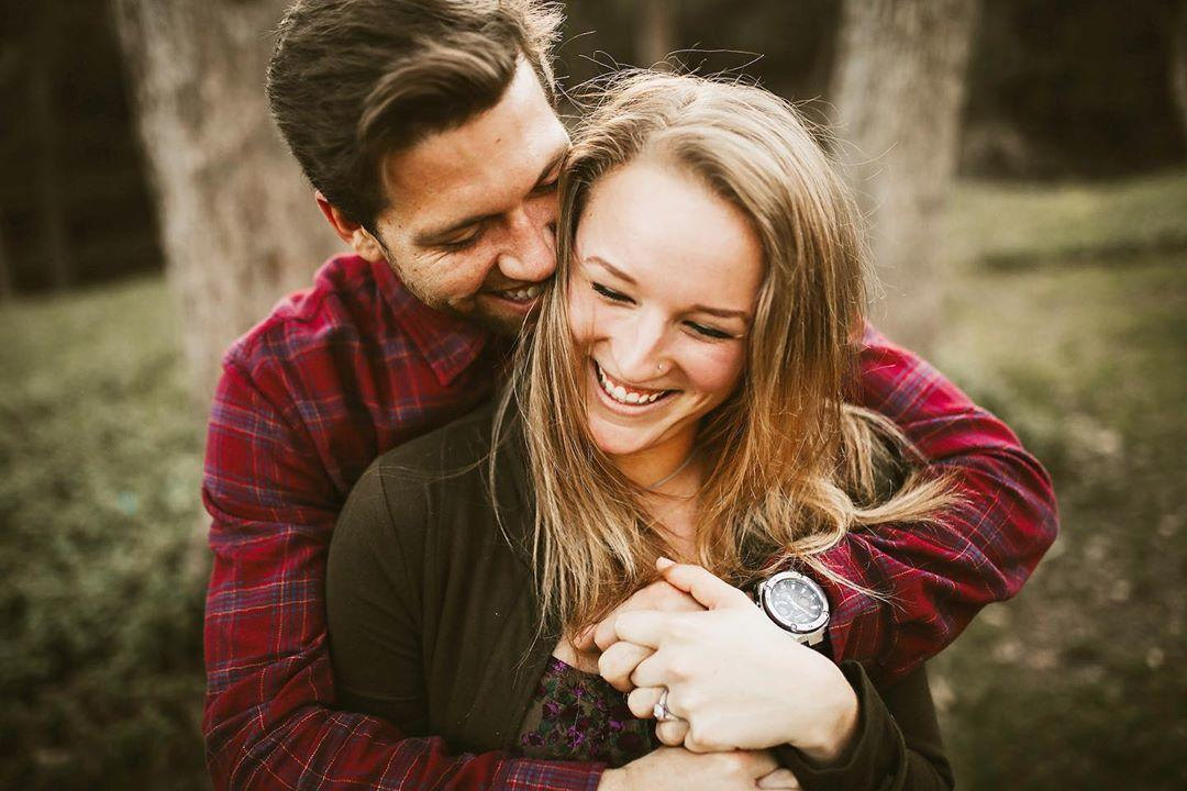 man hugging woman from behind and laughing by Brandi Allyse Photography