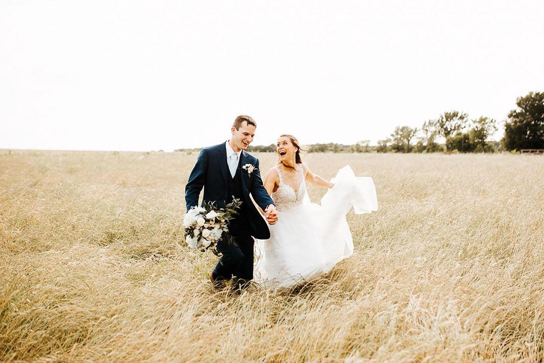 couple in wedding attire running in gold field and laughing while groom carries bouquet