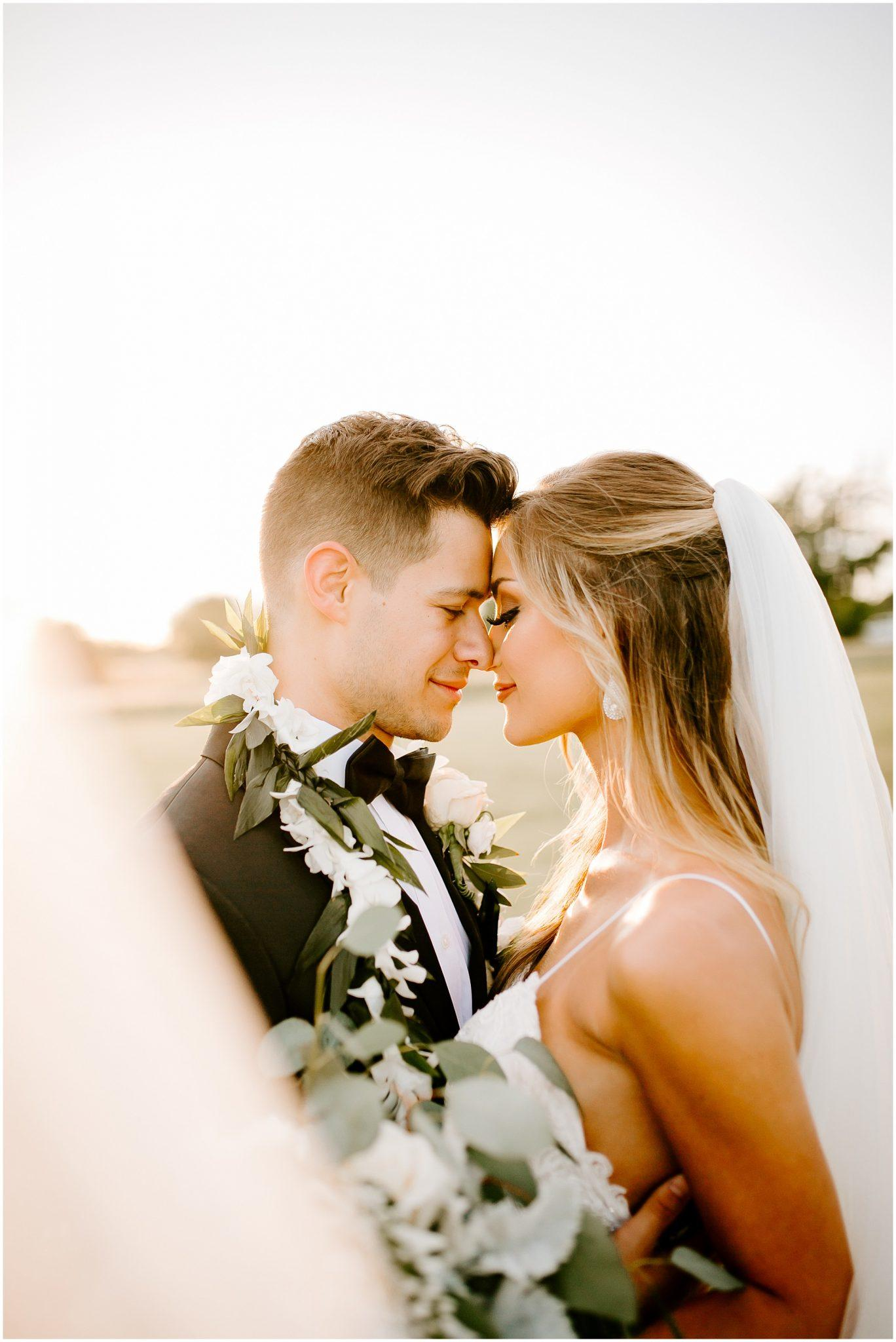 bride and groom nose to nose at sunset with flowers