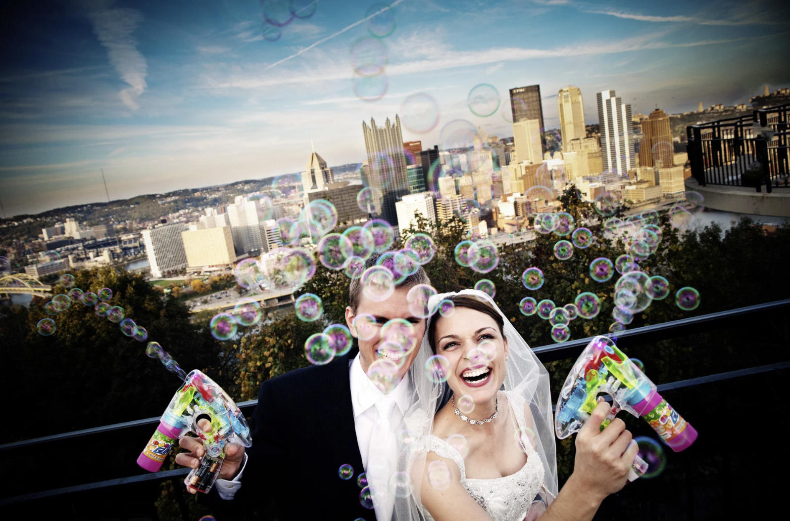 A wedding photo of a bride and groom blowing bubbles in the air after the ceremony, both overjoyed!