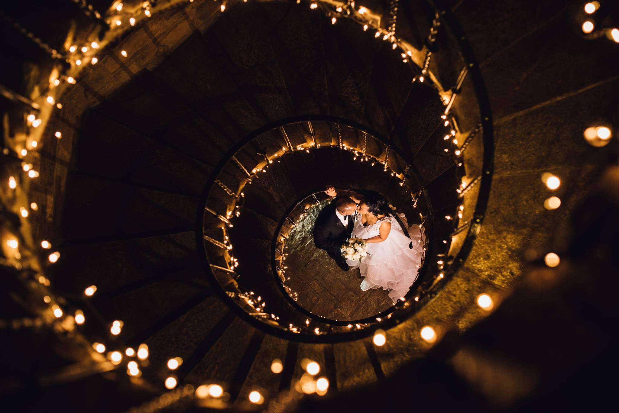 spiral staircase with twinkle lights and couple kissing at bottom