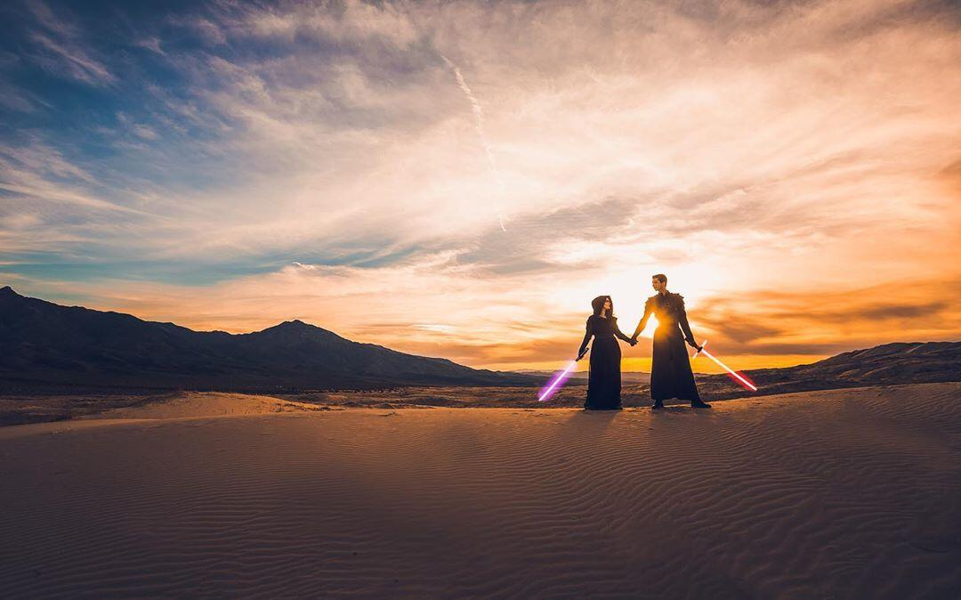 couples dressed up like Star Wars characters with light sabers in the desert