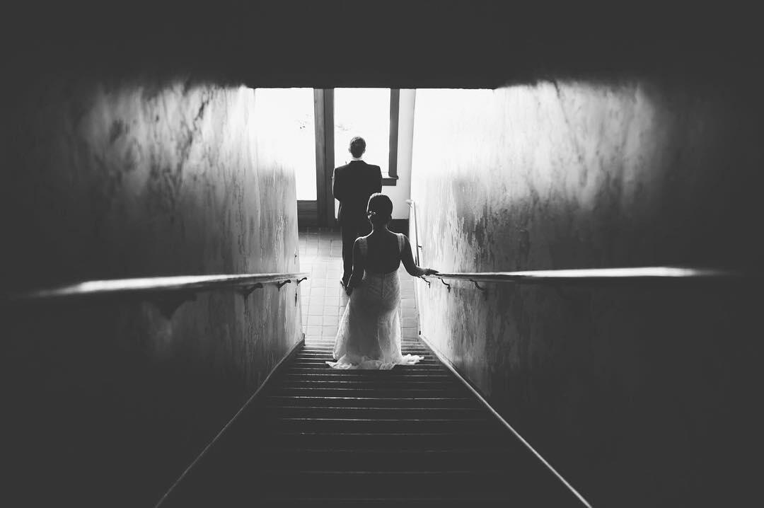 black and white image of bride approaching groom for first look