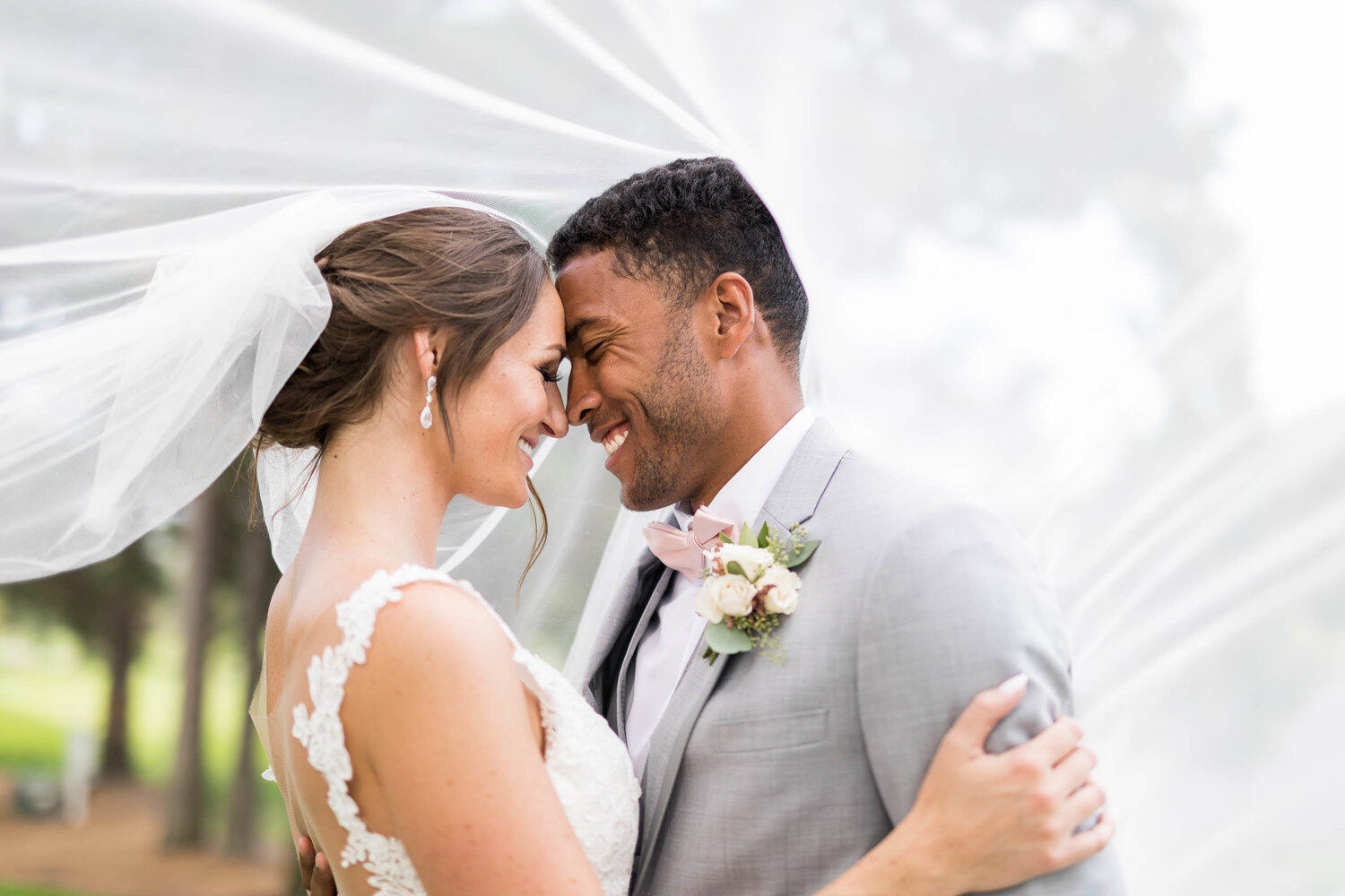 black groom and white bride leaning forehead to forehead under veil