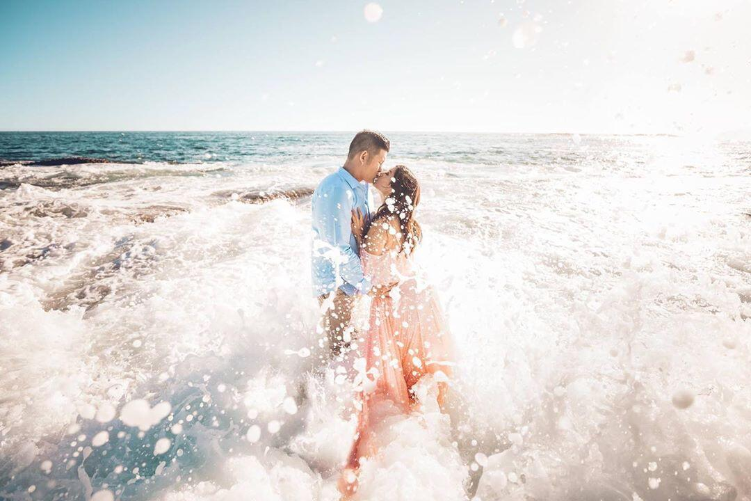 couple kissing in a crashing ocean wave