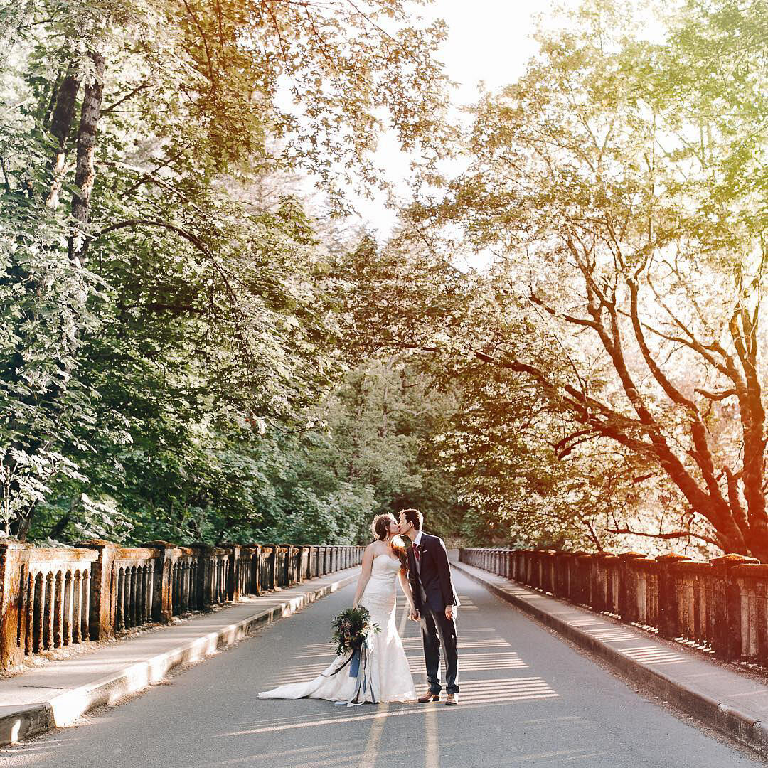 couple kissing on a bridge under trees cross processed look