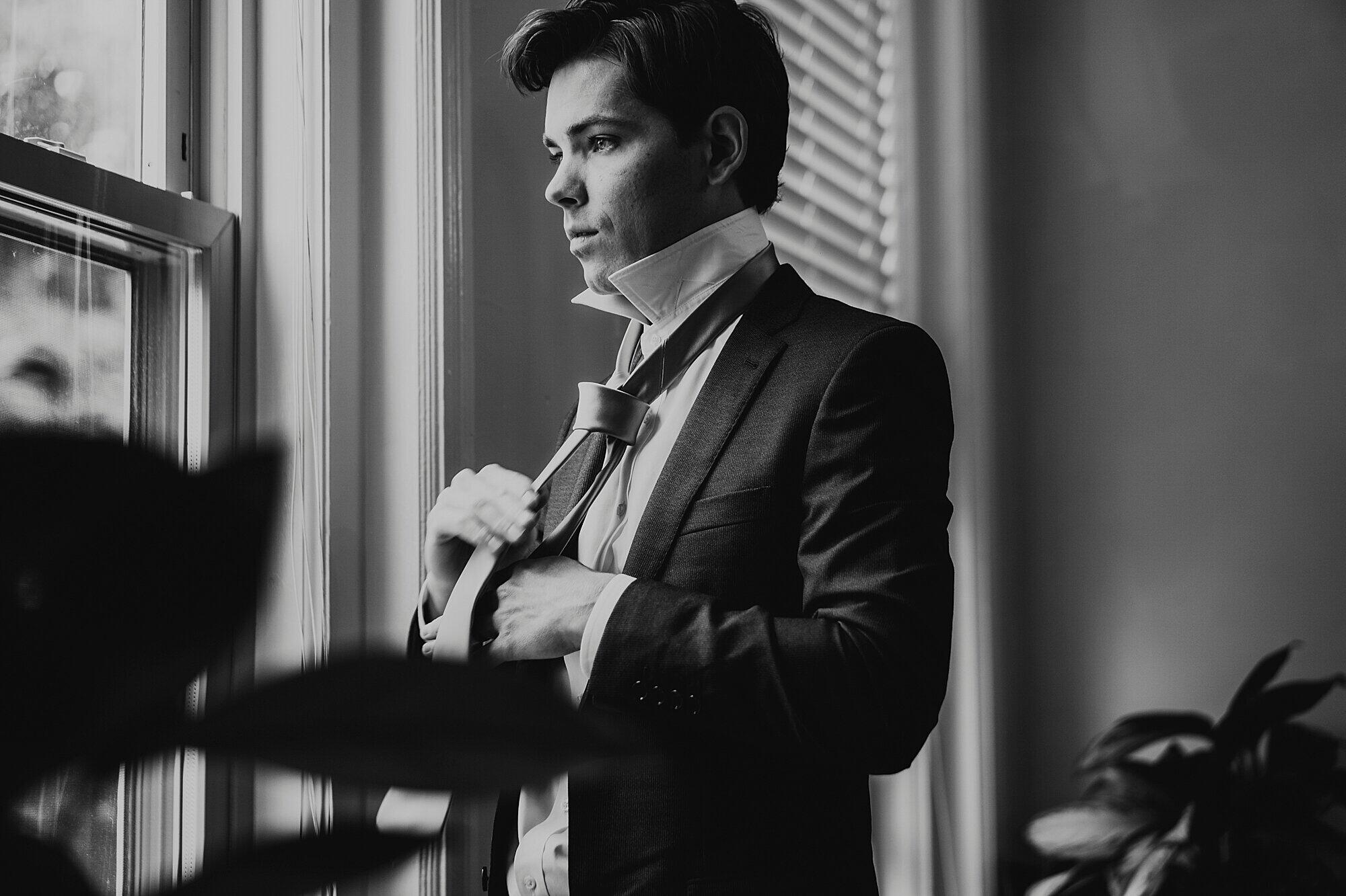 black and white photo of groom getting ready at window