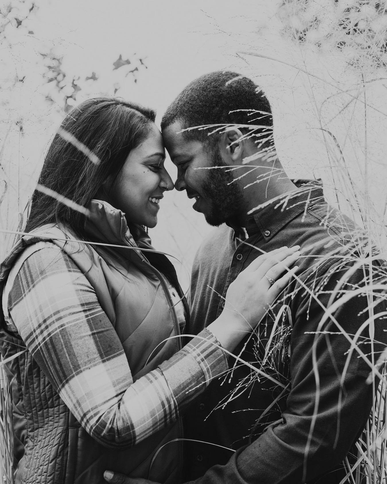 black and white photo of diverse couple nose to nose in a field of tall grass in the winter