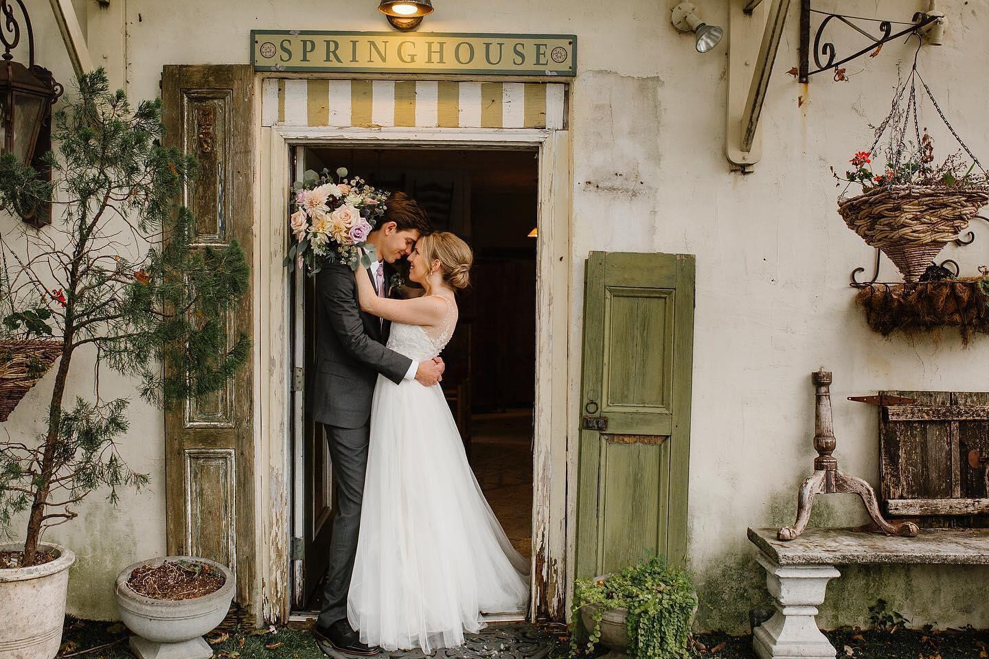 couple leaning together in doorway of a springhouse