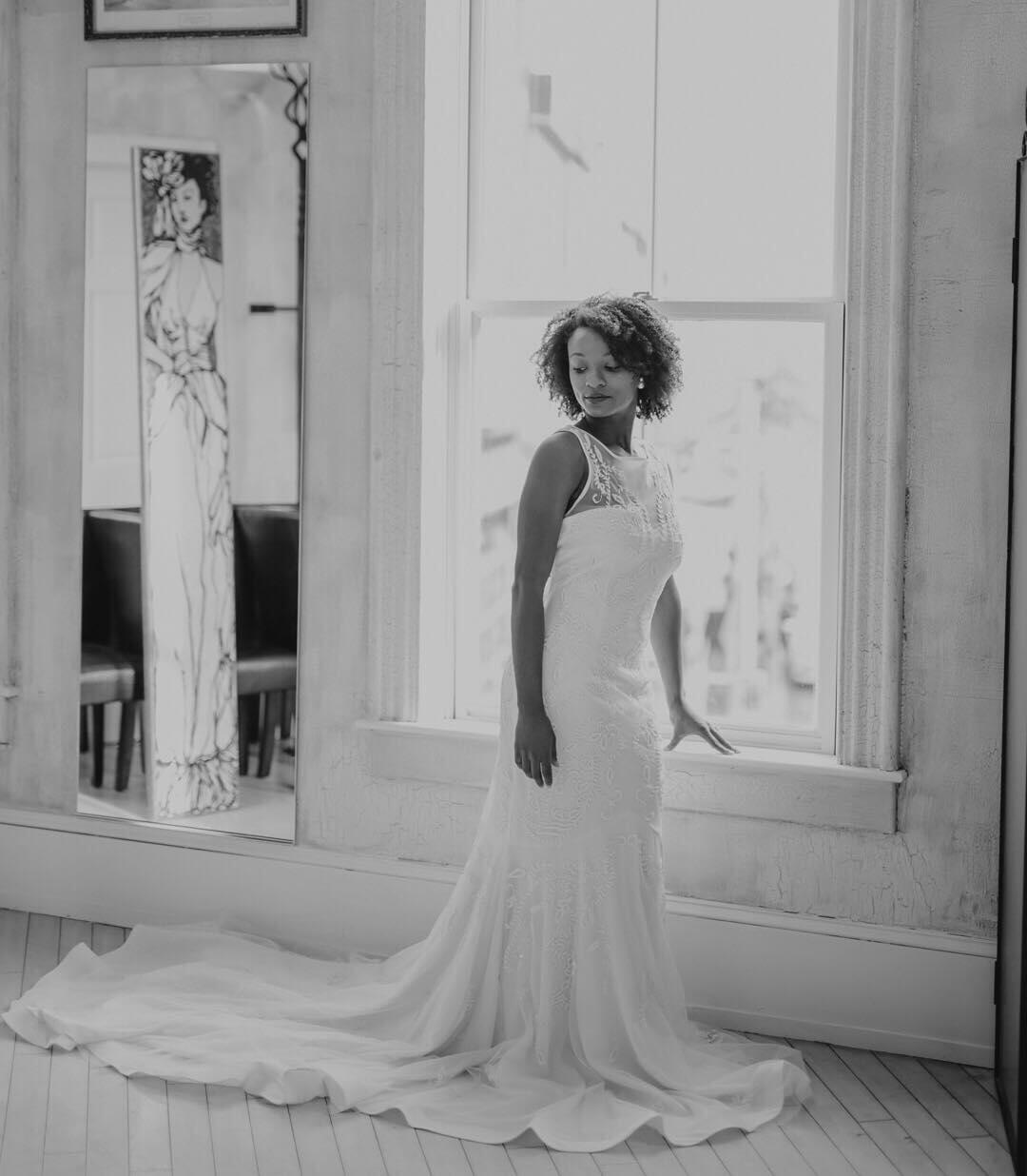 diverse black and white photo of woman in wedding dress posing by window