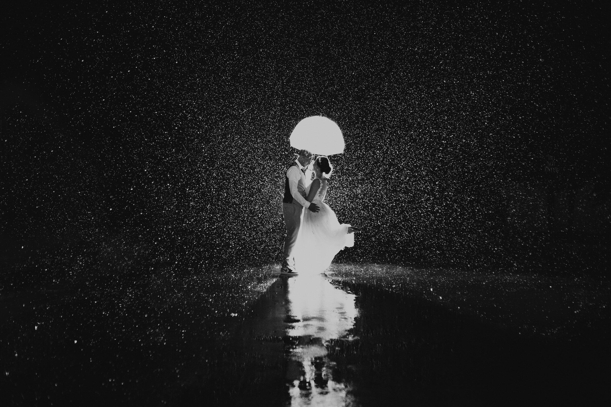couple under an umbrella with rain all around them