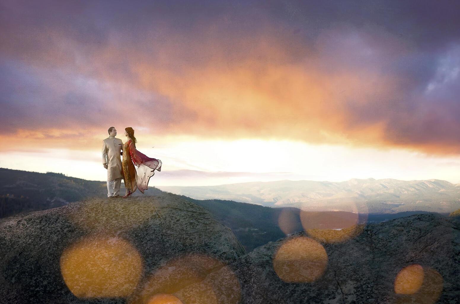 couple on rock ledge at sunset