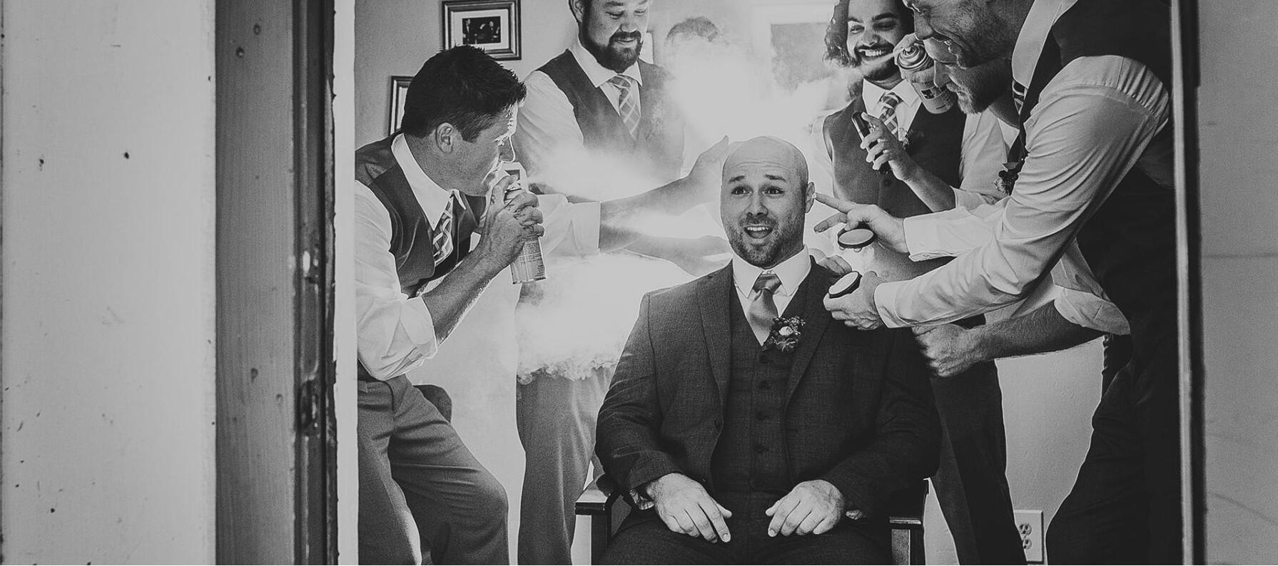 groom getting hairsprayed by groomsmen