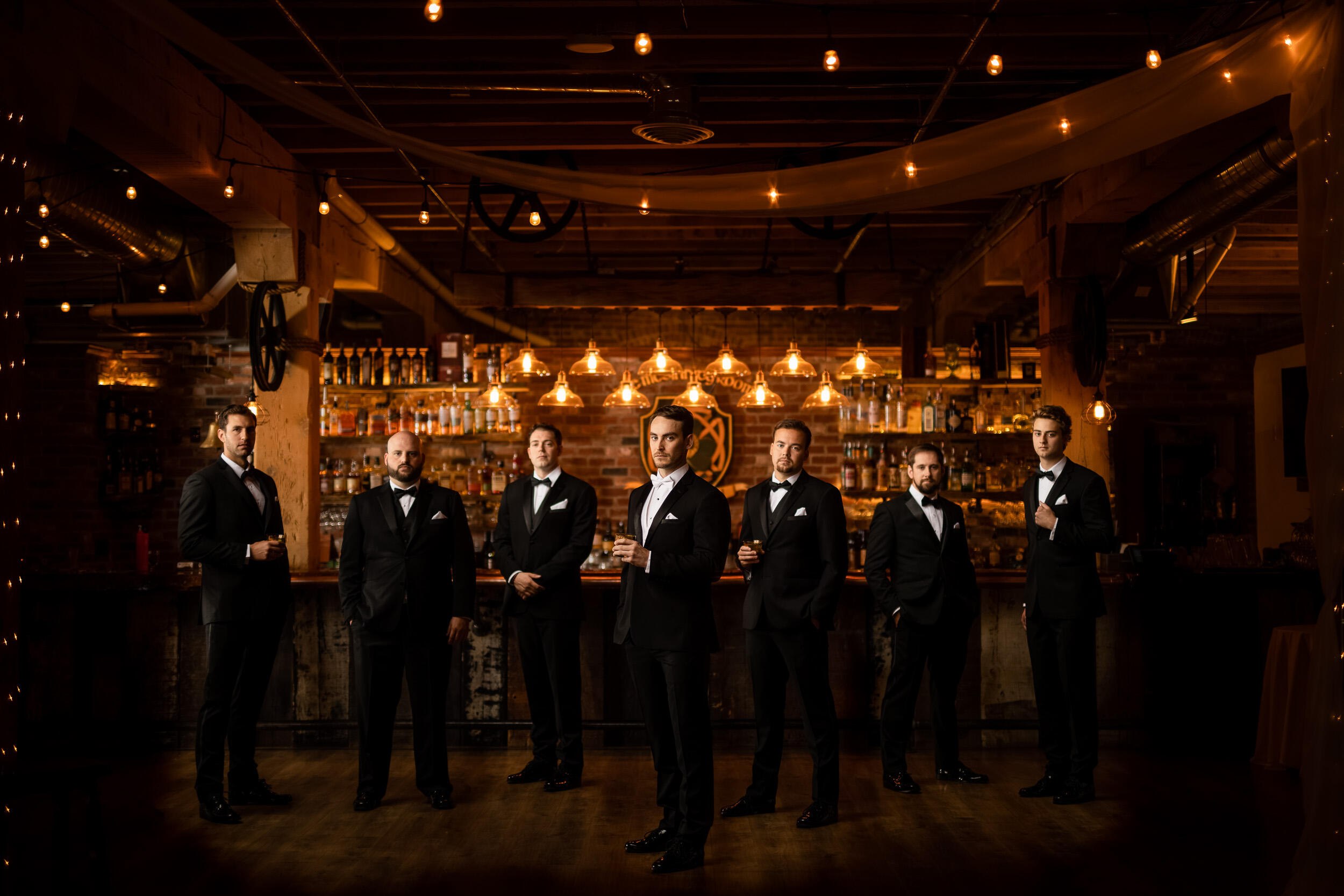 groomsmen standing at bar with groom