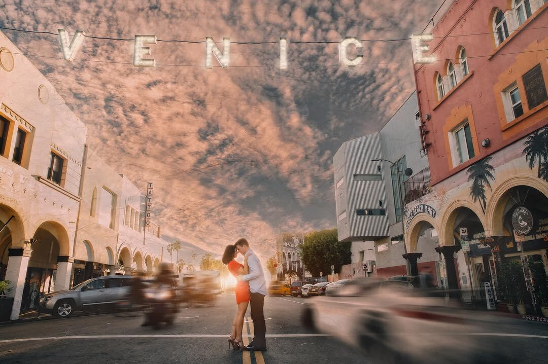 A couple posing for an engagement session in the middle of a road with LED Letter lights displaying - VENICE above them.